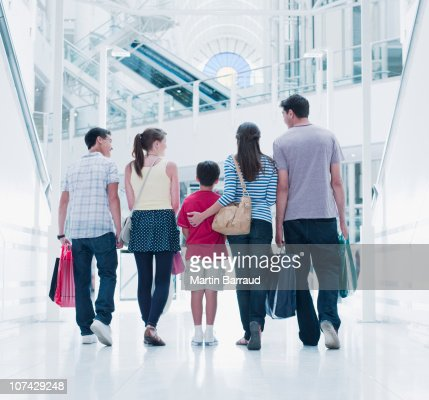 Famille portant des sacs de shopping au centre commercial : Photo