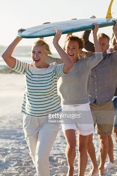 Family carrying surfboard on beach