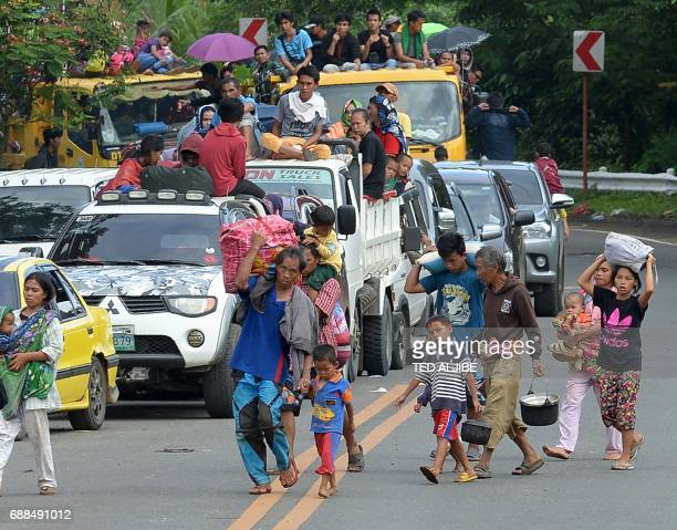 A family carrying their belongings walks in front of other residents in vehicles as they flee from Marawi on the southern island of Mindanao on May...