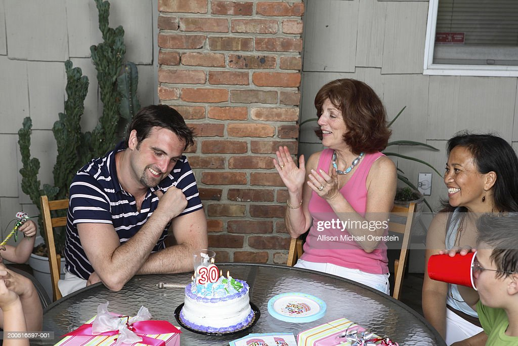 Family celebrating birthday at outdoor table : Stock Photo