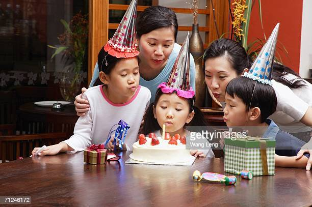 Family celebrating birthday, blowing candle