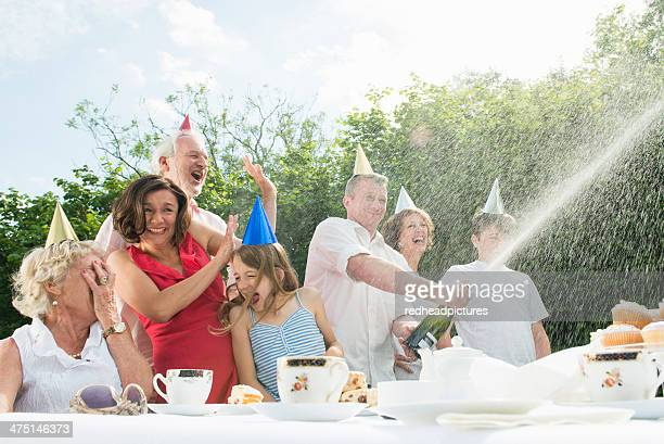Family celebrating birthday, man opening champagne