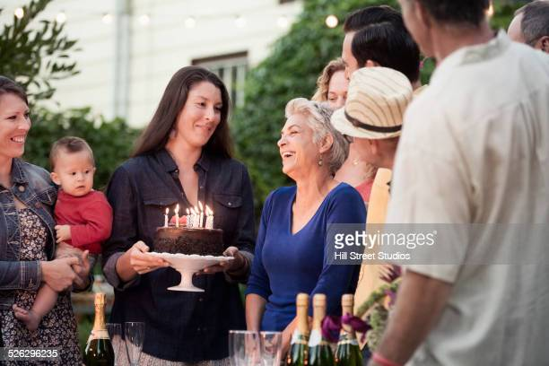 Family celebrating birthday together in backyard