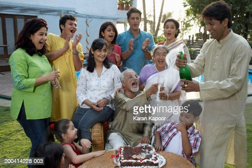 Family celebration, man holding overflowing champagne bottle, smiling : Foto de stock