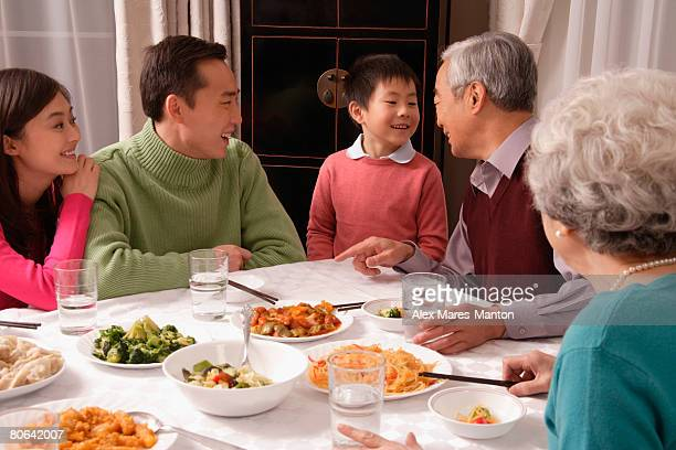 Family chatting over at dinner table having traditional food