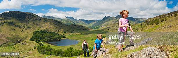 Family children climbing green mountain in idyllic landscape