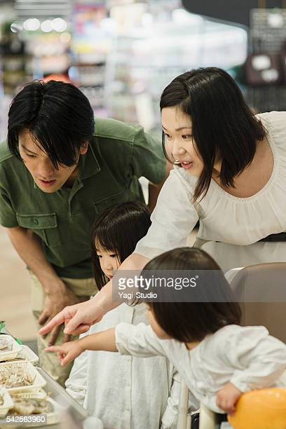 Family choosing fresh fish in fish department