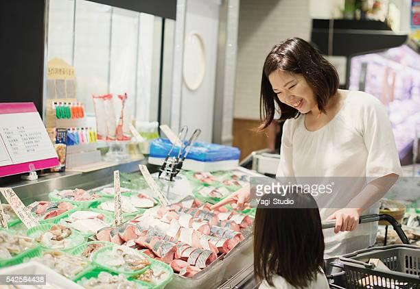 Family choosing fresh fish in fish department
