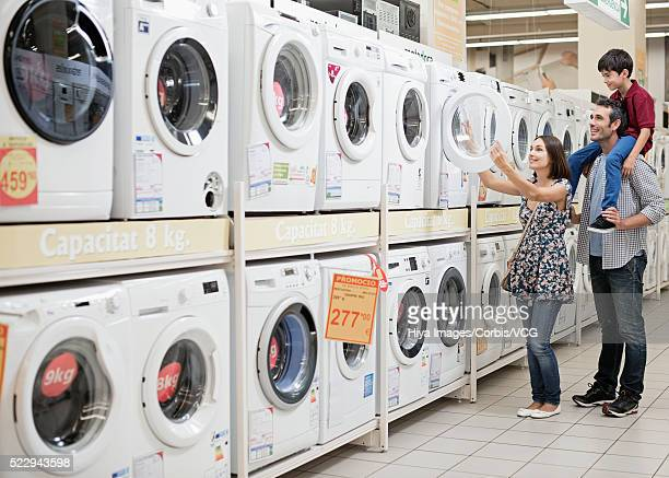 Family choosing washing machine in store