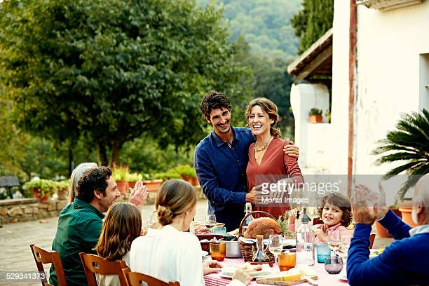 Family clapping for couple at outdoor meal table