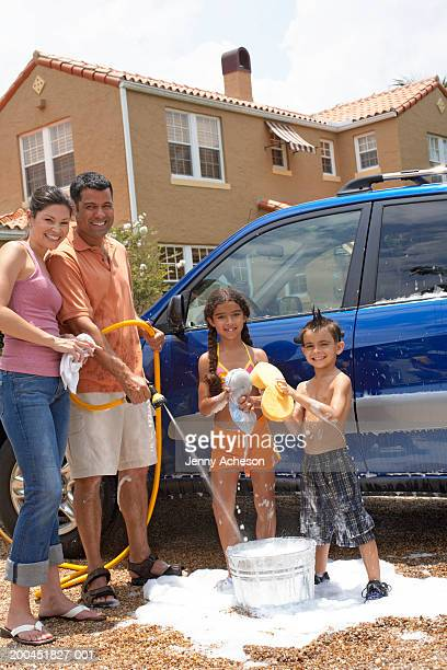 Family cleaning car, boy and girl (6-8) holding sponges, portrait