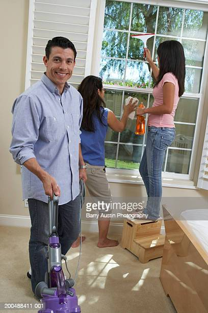 Family cleaning house, father vacuuming carpet, smiling, portrait