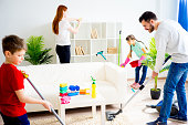 Happy family of four is cleaning their house