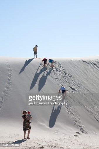 Family climbing sand dune : Stock Photo