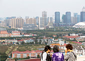 A family climbs up hills to see the constructions and cityscape On Dec 9 the central economic conference are held in Beijing It is estimated by...