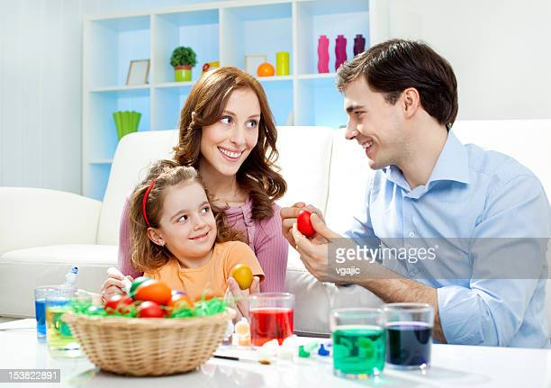 Familie malen Ostereier.