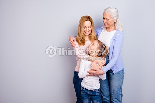 Family concept. Portrait of adorable lovely cute family generation standing hugging together wearing casual clothed isolated on gray background copyspace : Stock Photo