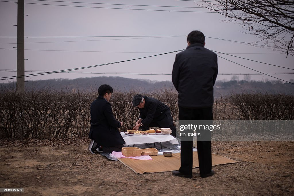 A family conduct a memorial service for relatives in the North, before a barbed wire fence near the Demilitarized Zone (DMZ) separating North and South Korea, in Imjingak on February 8, 2016. Some South Korean families separated during the Korean war visited the DMZ to offer prayers to their relatives in the North on the occasion of the Lunar New Year. AFP PHOTO / Ed Jones / AFP / ED JONES