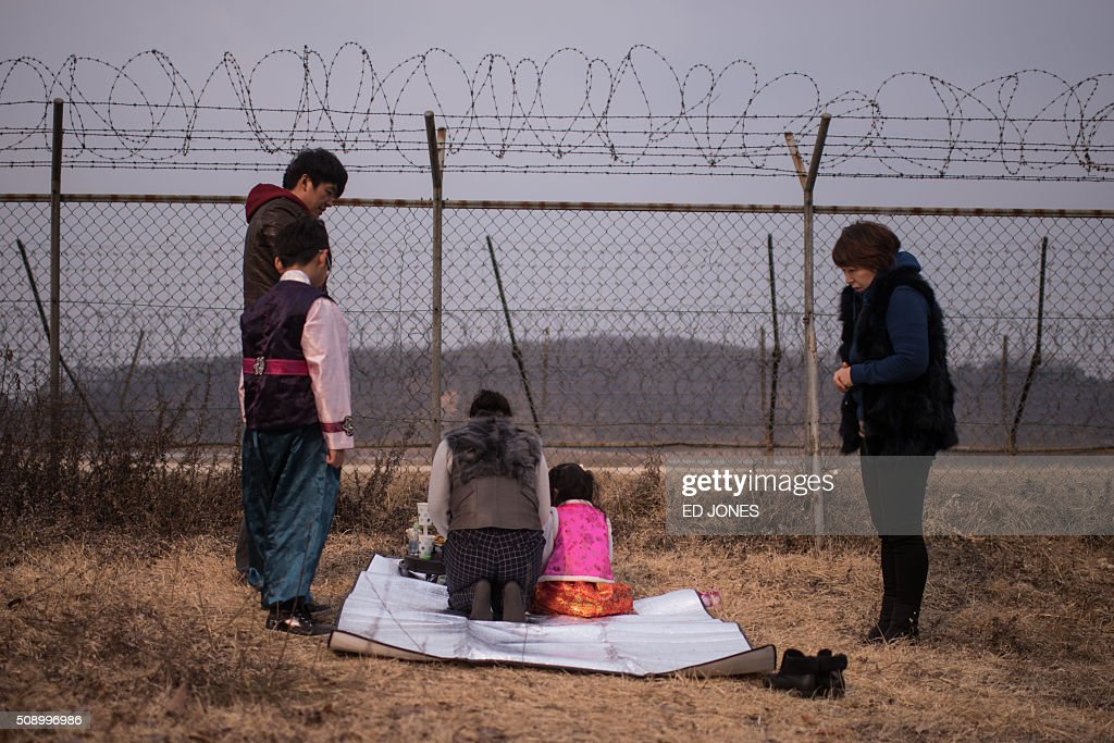 A family conduct a memorial service for relatives in the North before a barbed wire fence near the Demilitarized Zone (DMZ) separating North and South Korea, in Imjingak on February 8, 2016. Some South Korean families separated during the Korean war visited the DMZ to offer prayers to their relatives in the North on the occasion of the Lunar New Year. AFP PHOTO / Ed Jones / AFP / ED JONES
