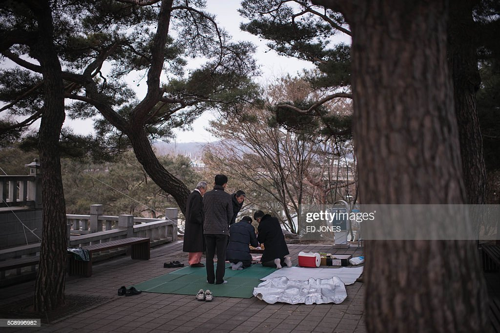 A family conduct a memorial service for relatives in the North near the Demilitarized Zone (DMZ) separating North and South Korea, in Imjingak on February 8, 2016. Some South Korean families separated during the Korean war visited the DMZ to offer prayers to their relatives in the North on the occasion of the Lunar New Year. AFP PHOTO / Ed Jones / AFP / ED JONES