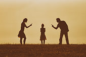 Silhouette of a angry mother and father scolding their daughter.Image is intentionally with grain and toned.