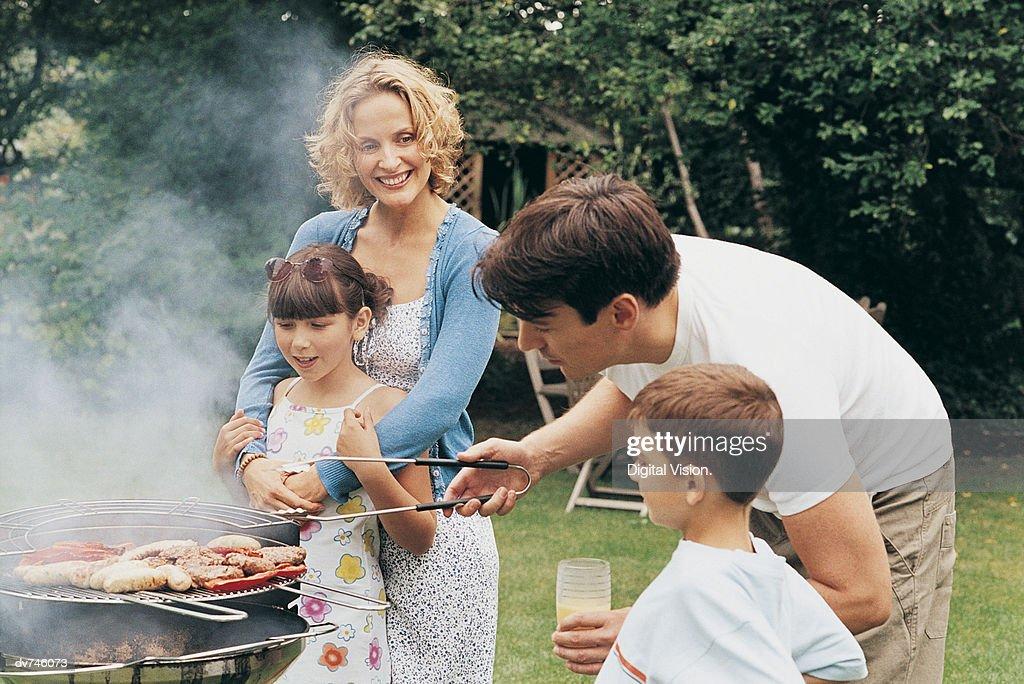 Family Cooking A Barbecue in Their Garden : Stock Photo
