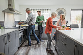 Siblings are helping their senior parents to cook a meal in their home while socialising.