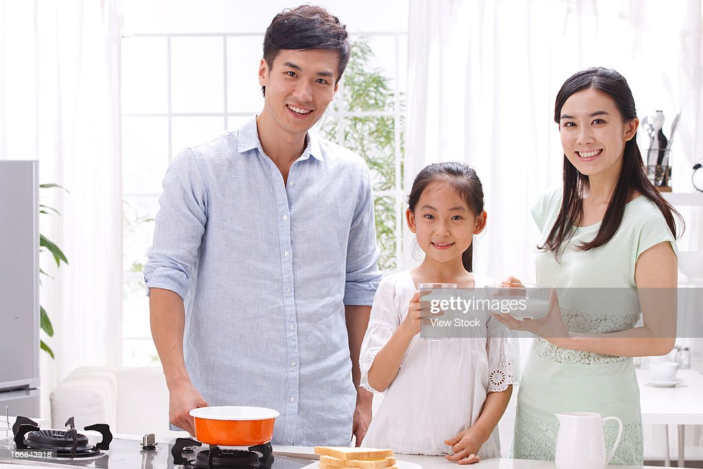 Family cooking breakfast in kitchen : Stock Photo