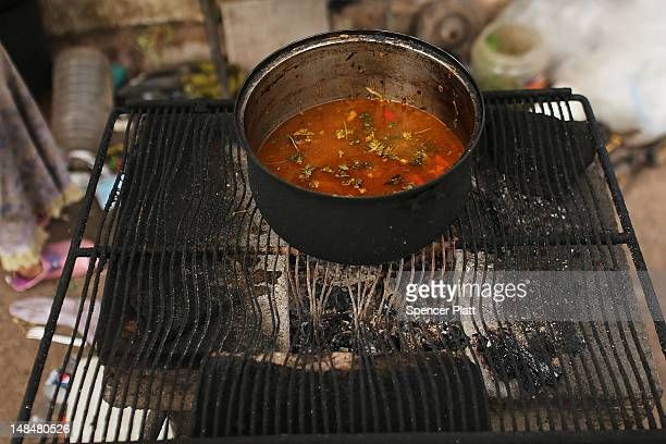 A family cooks their dinner on an outdoor charcoal stove beside a dumpster in a gang infested neighborhood on July 17 2012 in Tegucigalpa Honduras...
