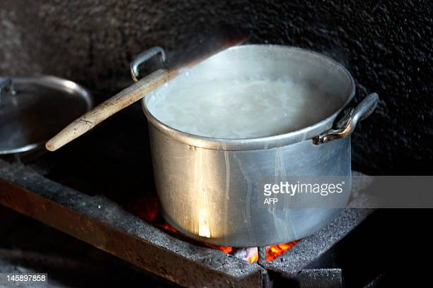 A family cooks with a common charcoalfueld stove in the Mozambican capital Maputo on May 19 2012 These charcoal stoves are the most common kinds of...