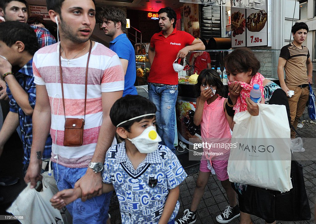 A family covers their faces because of tear gas, as Turkish police battle anti-government protestors along the Istiklal shopping street near Taksim Square on July 8, 2013 in Istanbul, Turkey. The protests began in late May over the Gezi Park redevelopment project and saving the park trees adjacent to Taksim Square but swiftly turned into a protest aimed at Prime Minister Recep Tayyip Erdogan and what protestors call his increasingly authoritarian rule. The protest spread to dozens of cities in Turkey, in secular anger against Mr. Erdogan and his Islam-rooted Justice and Development Party (AKP).