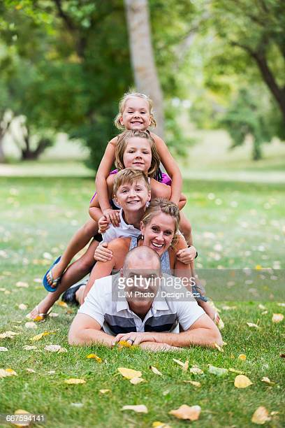 A family creating a totem pole picture by climbing on top of each other in a park
