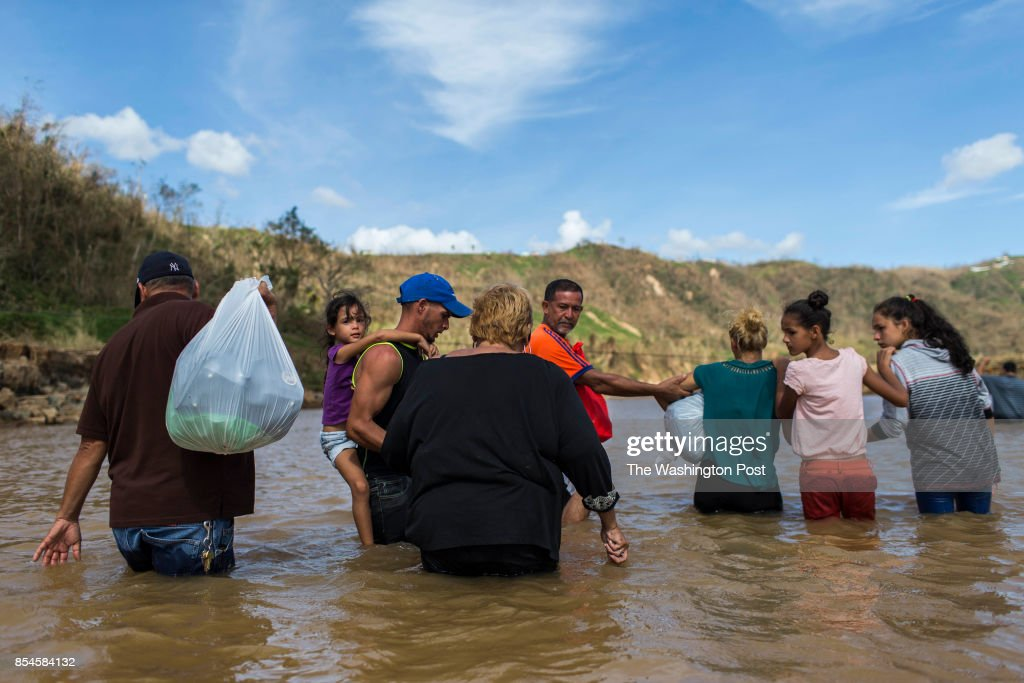 A family cross the San Lorenzo River in Morovis. Residents of San Lorenzo neighborhood can't access their houses because the river destroyed the bridge that communicate them with the main road of access. The mountain town of Morovis, in the south west of San Juan, is one of the most affected after the pass of Hurricane María. Hurricane Maria passed through Puerto Rico leaving behind a path of destruction across the national territory.