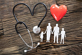 Elevated View Of Family Cut Out And Red Heart With Stethoscope On Desk