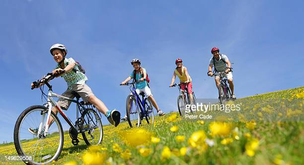 family cycling downhill in field
