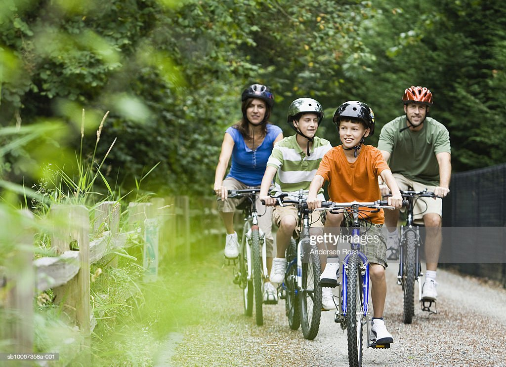 Family cycling in park : Stock Photo