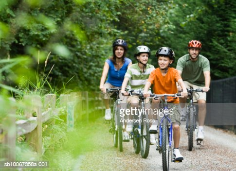 Family cycling in park : Bildbanksbilder