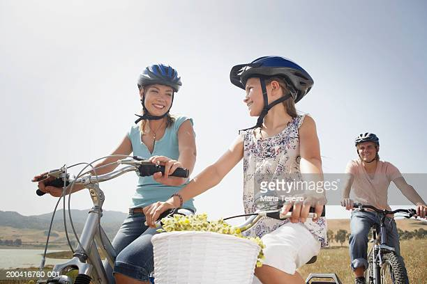 Family cycling, mother smiling at daughter (9-11), low angle view