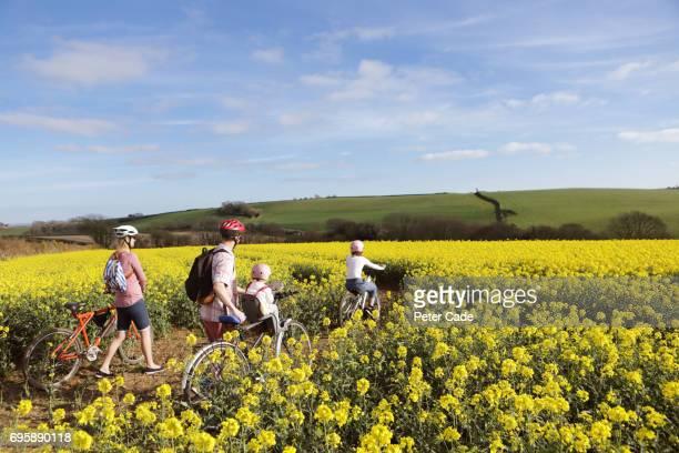 Family cycling through rape seed field