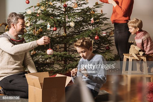 People Decorating For Christmas father and son decorating christmas tree stock photo | getty images