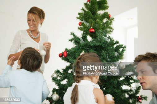 People Decorating For Christmas family decorating christmas tree stock photo | getty images