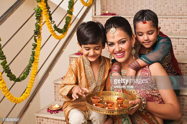 Family decorating with oil lamps on Diwali