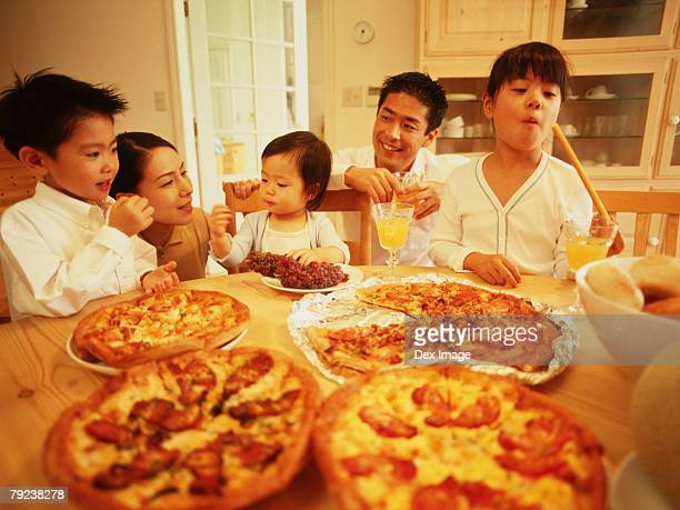 Family dining, table full of pizza
