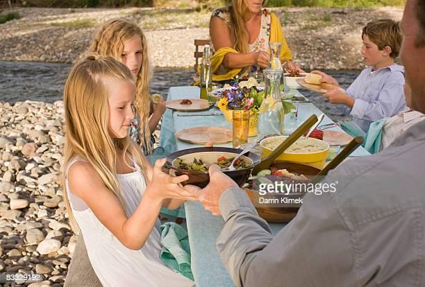 Family dinner outside by river
