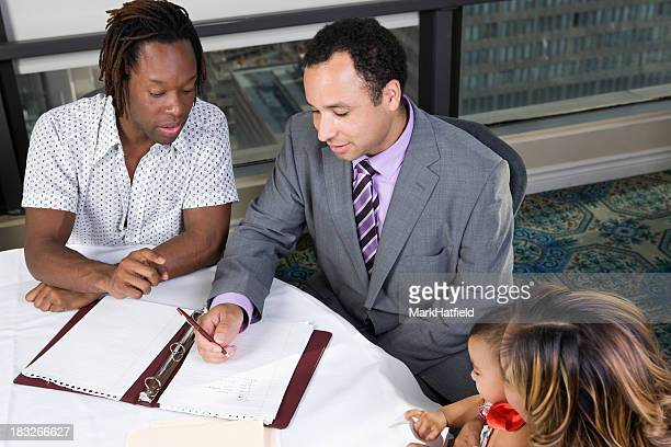 Family discussing college at a table with financial planner