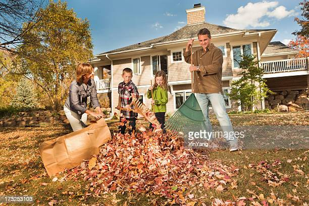 Family Doing Autumn Outdoor Leave Raking Work Together