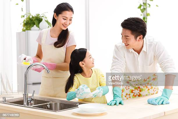 Family doing cleaning-up in kitchen