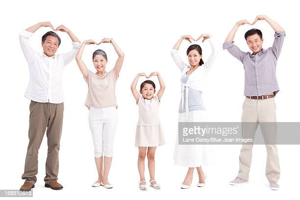 Family doing heart-shaped gesture