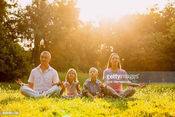 Famille faire du yoga dans le parc