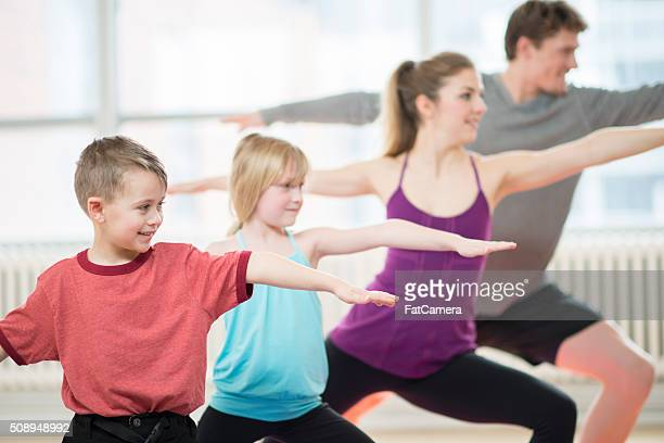 Famille faisant Yoga ensemble dans la salle de sport